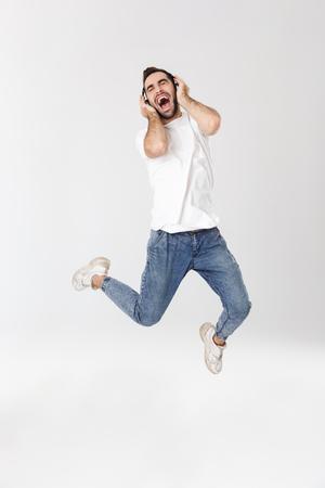 Longitud total de un apuesto hombre alegre con camiseta en blanco que se encuentran aisladas sobre fondo blanco, escuchando música con auriculares Foto de archivo