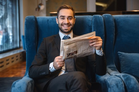 Handsome pensive young businessman wearing suit sitting at the hotel lobby, reading newspaper