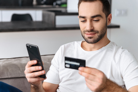 Photo of caucasian guy 30s in casual t-shirt using smartphone and holding credit card for online shopping while sitting on sofa at home