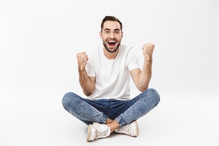 In voller Länge eines fröhlichen jungen Mannes, der mit gekreuzten Beinen sitzt, isoliert auf weißem Hintergrund und Erfolg feiert