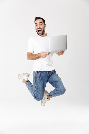 Full length of a handsome cheerful man wearing blank t-shirt jumping isolated over white background, using laptop computer
