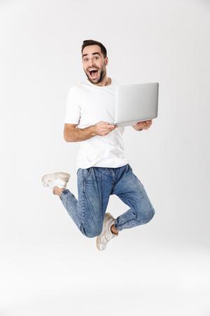 Toute la longueur d'un bel homme gai portant un t-shirt vierge sautant isolé sur fond blanc, à l'aide d'un ordinateur portable