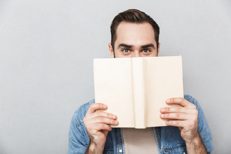 Young man wearing shirt isolated over gray background, covers face with opened book Stok Fotoğraf - 123310105