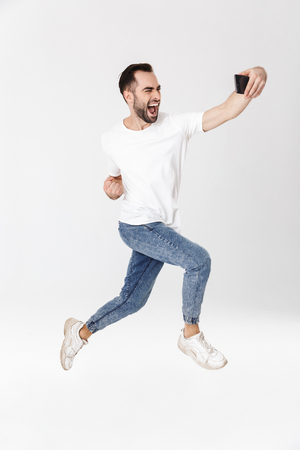 Full length of a handsome cheerful man wearing blank t-shirt jumping isolated over white background, taking a selfie