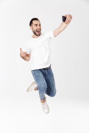 Longitud total de un apuesto hombre alegre vestido con camiseta en blanco saltando aislado sobre fondo blanco, tomando un selfie