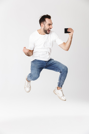 Full length of a handsome cheerful man wearing blank t-shirt standing isolated over white background, playing games on mobile phone, jumping