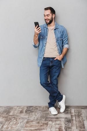 Volledige lengte van een opgewonden vrolijke man met shirt over grijze achtergrond, met behulp van mobiele telefoon mobile Stockfoto