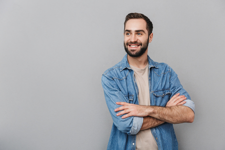 Excited cheerful man wearing shirt isolated over gray background, arms folded