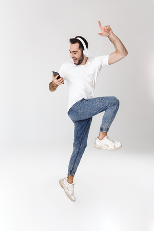 Full length of a handsome cheerful man wearing blank t-shirt standing isolated over white background, listening to music with headphones, using mobile phone