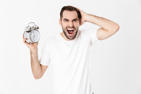 Handsome angry man wearing blank t-shirt standing isolated over white background, showing alarm clock, screaming