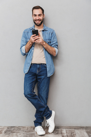 Full length of an excited cheerful man wearing shirt over gray background, using mobile phone