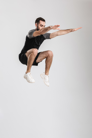 Full length portrait of a confident young sportsman jumping isolated over white background Archivio Fotografico
