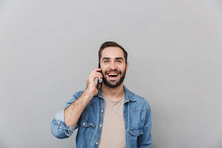 Excited cheerful man wearing shirt isolated over gray background, talking on mobile phone