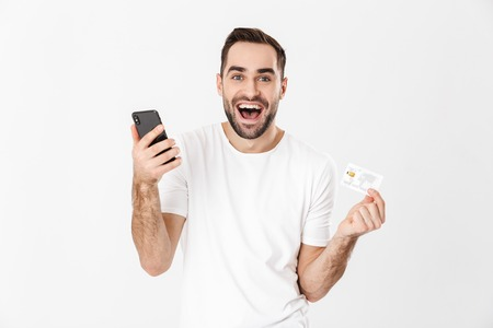 Apuesto hombre alegre vistiendo camiseta en blanco que se encuentran aisladas sobre fondo blanco, mediante teléfono móvil, mostrando tarjeta de crédito de plástico
