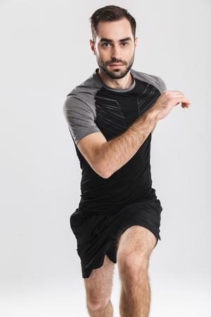 Confident motivated sportsman running isolated over white