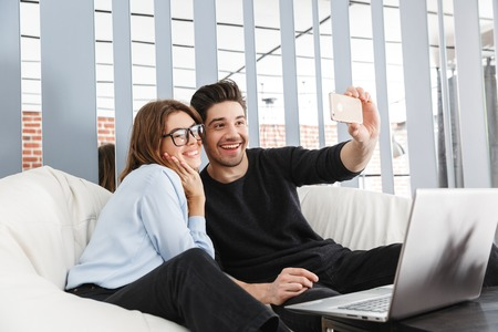 Image of a happy young loving couple at home indoors using laptop computer make a selfie by phone.