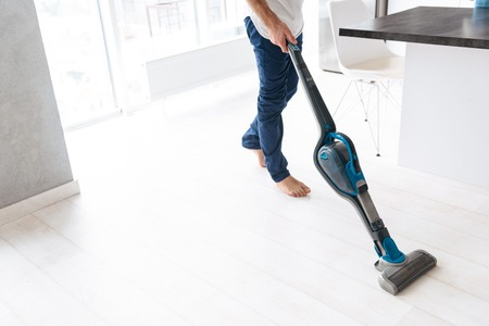 Close up of a man vacuuming the floor at the kitchen Banco de Imagens - 123311738