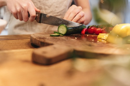 Close up of a woman chopping vegetables on a wooden board Reklamní fotografie