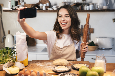 Cheerful young woman wearing apron preparing dough for an apple pie at the kitchen at home, taking a selfie, holding rolling pin Reklamní fotografie
