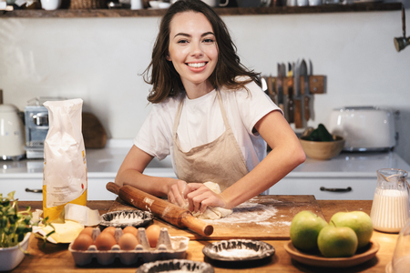 Cheerful young woman wearing apron preparing dough for an apple pie at the kitchen at home Фото со стока