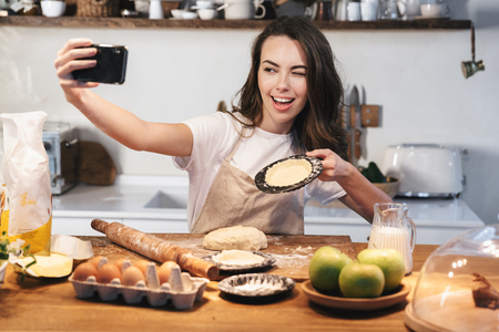 Cheerful young woman wearing apron preparing dough for an apple pie at the kitchen at home, taking a selfie