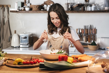 Beautiful young woman wearing apron cooking healthy salad at the kitchen at home, mixing
