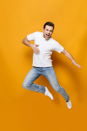 Full length portrait of a happy young man wearing t-shirt jumping isolated over yellow background, celebrating