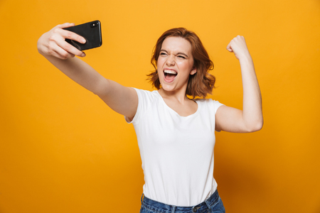 Portrait of a happy lovely girl standing isolated over yellow background, taking a selfie, flexing biceps Stock Photo