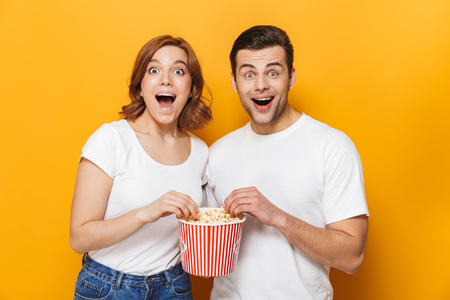 Excited beautiful couple wearing white t-shirts standing isolated over yellow background, eating popcorn
