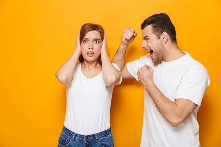 Angry beautiful couple wearing white t-shirts standing isolated over yellow background, having a fight