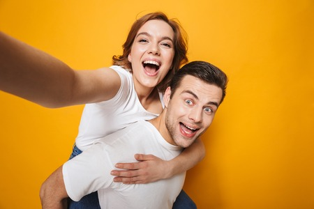 Portrait of a cheerful young couple standing isolated over yellow background, piggyback ride, taking selfie Stockfoto - 123312272