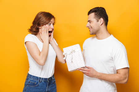 Portrait of a cheerful young couple standing isolated over yellow background, happy man giving his girlfriend present box Фото со стока