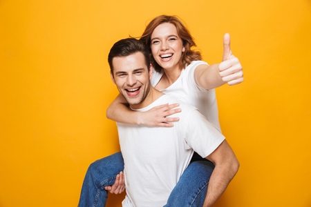 Portrait of a cheerful young couple standing isolated over yellow background, piggyback ride, thumbs up Stockfoto