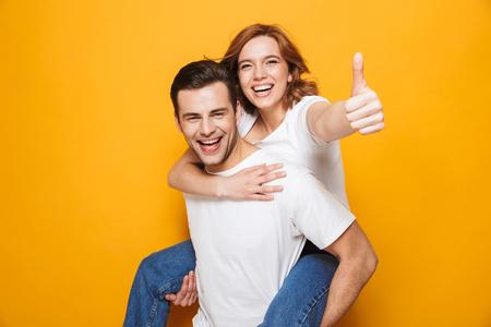 Portret wesołej młodej pary stojącej odizolowanej na żółtym tle, przejażdżka na barana, kciuk w górę