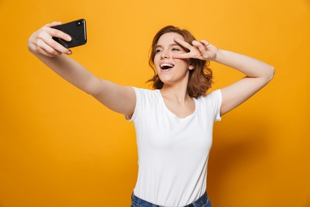 Portrait of a happy lovely girl standing isolated over yellow background, taking a selfie