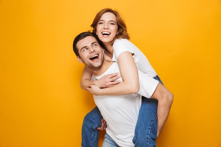 Portrait of a cheerful young couple standing isolated over yellow background, piggyback ride