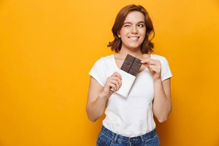Portrait of a happy lovely girl standing isolated over yellow background, holding chocolate bar Stock Photo
