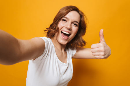 Portrait of a happy lovely girl standing isolated over yellow background, taking a selfie, thumbs up Stock Photo