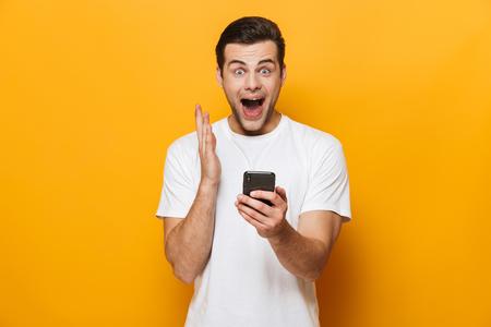 Portrait d'un jeune homme heureux portant un t-shirt debout isolé sur fond jaune, utilisant un téléphone portable, célébrant le succès Banque d'images