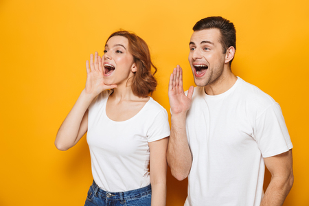 Portrait of a cheerful young couple standing isolated over yellow background, screaming loud