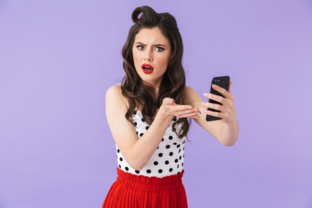 Photo of displeased pin-up woman 20s in vintage polka dot dress holding and using black smartphone isolated over violet background