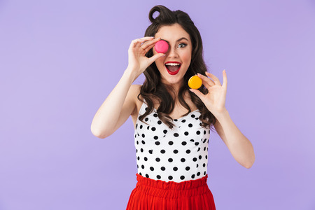 Photo of cheery pin-up woman 20s in vintage polka dot dress rejoicing while holding and eating macaron cookies isolated over violet background 写真素材