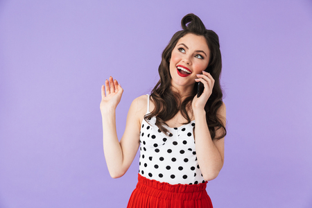 Photo of young pin-up woman 20s in vintage polka dot dress holding and using black smartphone isolated over violet background