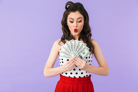 Portrait of rich pin-up woman 20s in vintage polka dot dress smiling while holding bunch of money banknotes isolated over violet background