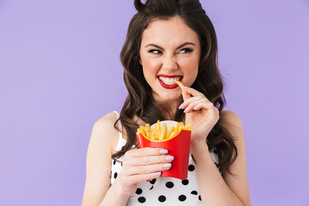 Photo of caucasian pin-up woman 20s in vintage polka dot dress having dinner and eating french fries isolated over violet background 스톡 콘텐츠
