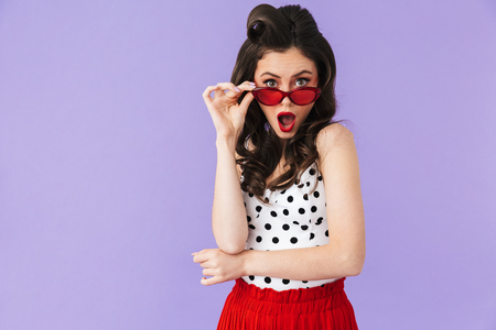 Portrait of brunette pin-up woman 20s in vintage polka dot dress and retro sunglasses smiling at camera isolated over violet background 写真素材