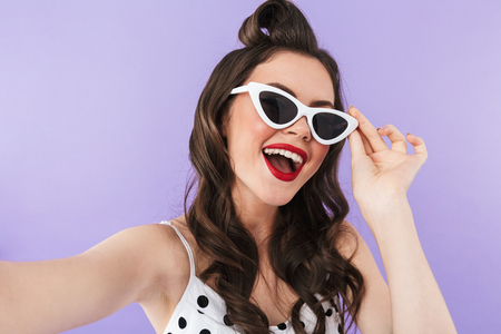 Portrait of gorgeous pin-up woman 20s in vintage polka dot dress and retro sunglasses smiling at camera isolated over violet background 免版税图像