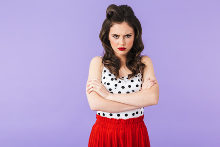 Portrait of resentful pin-up woman 20s in vintage polka dot dress looking at camera with anger isolated over violet background