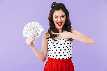 Portrait of a beautiful pin-up girl wearing bright makeup standing isolated over violet background, showing money banknotes