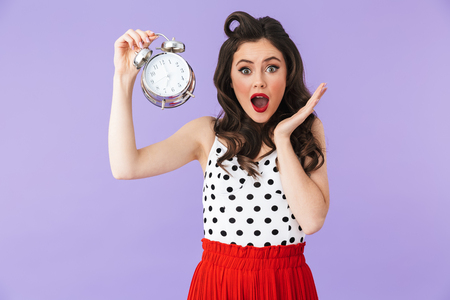Portrait of brunette pin-up woman 20s in retro polka dot dress holding alarm clock isolated over violet background